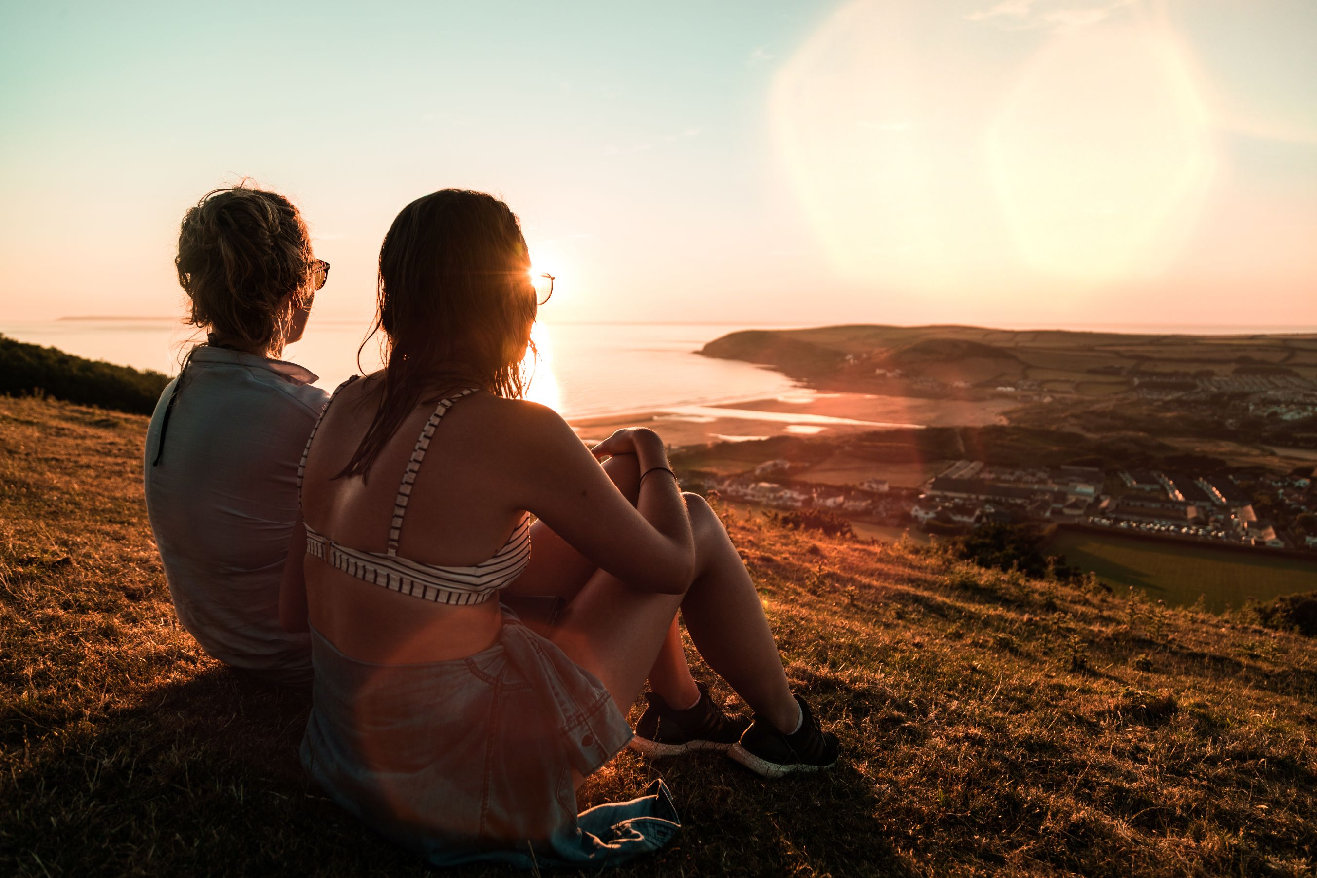 Two girls sitting on hillside looking over seaside village.