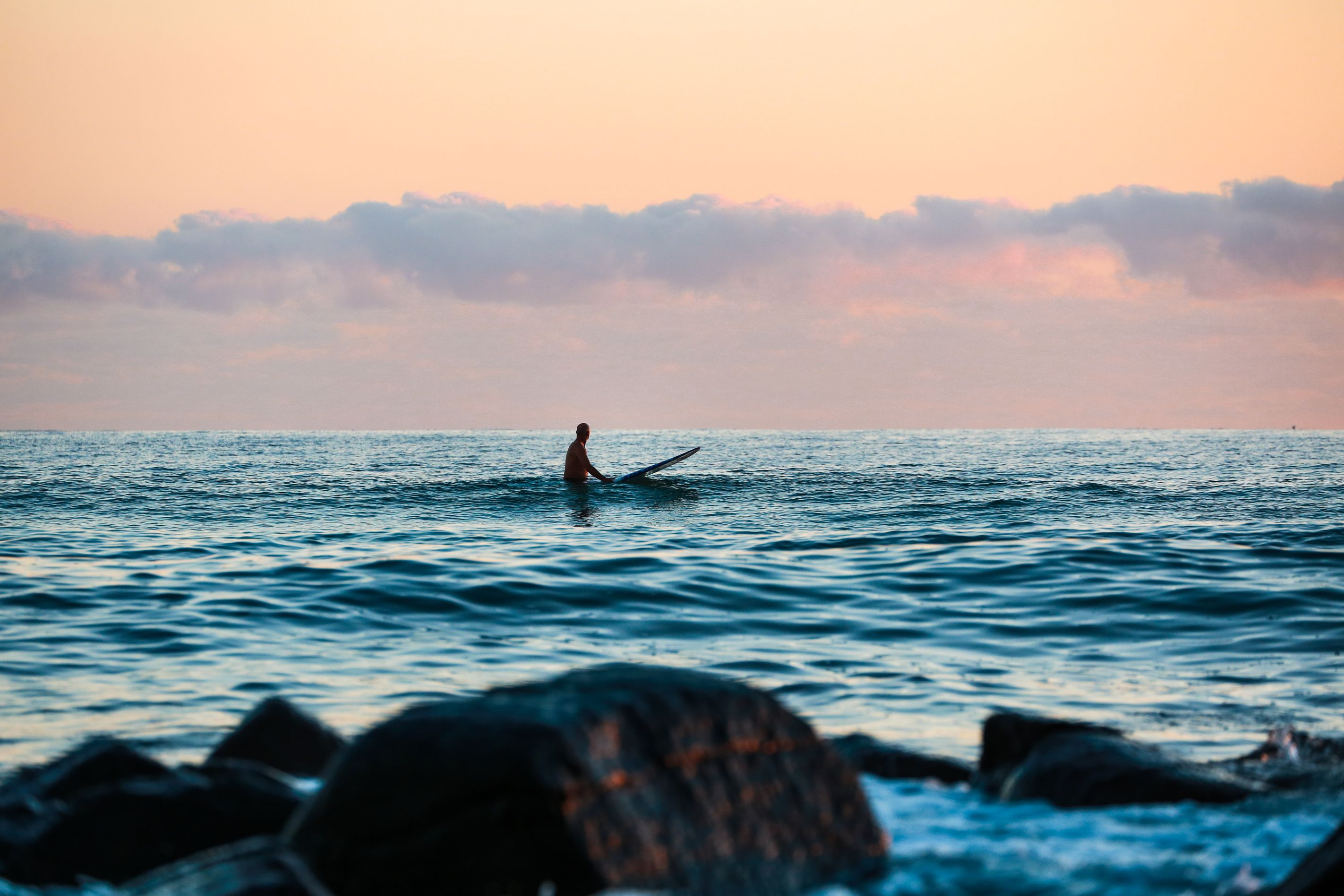 Surfer waiting in the water for a wave at sunset.