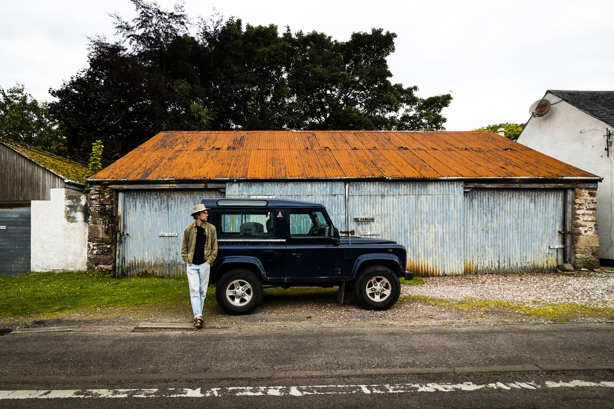 Man standing against Land Rover defender.