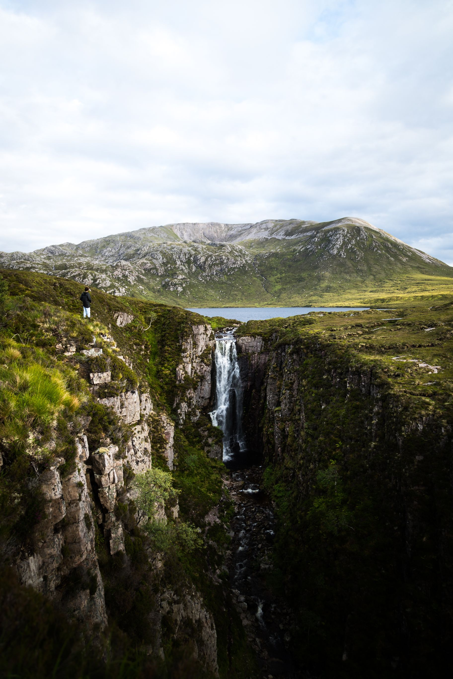 Man looking over waterfall in the Scottish Highlands