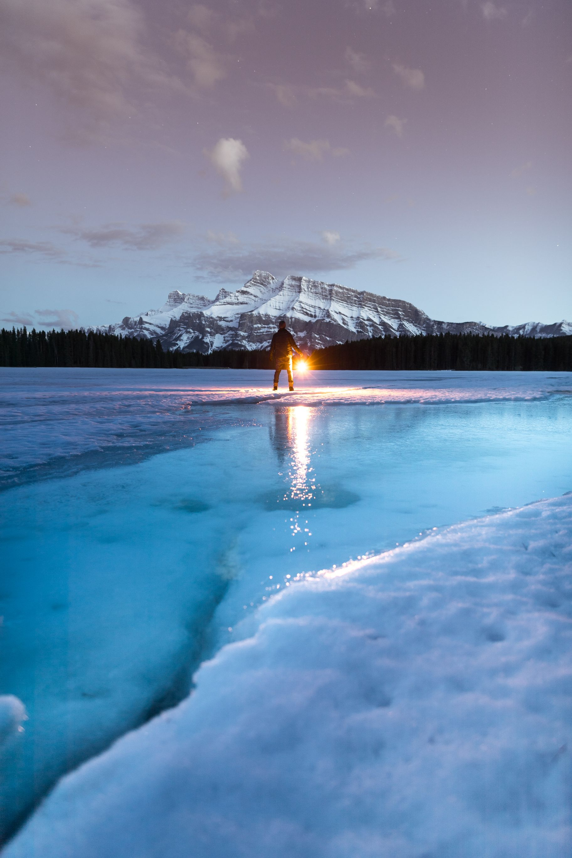 A man standing on a half frozen lake holding a lamp.