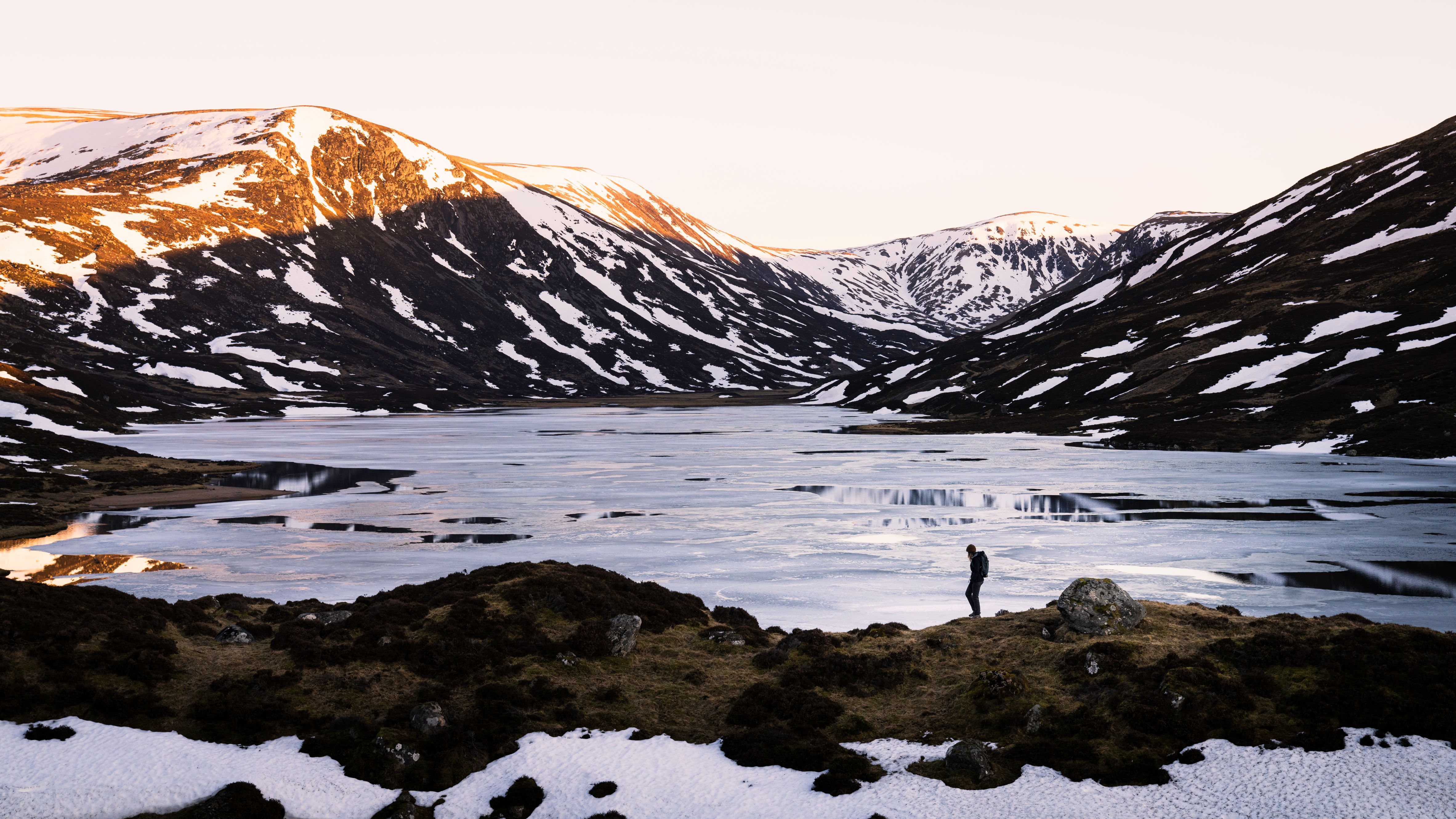 Figure on top of rocks overlooking lake and snowy mountains.