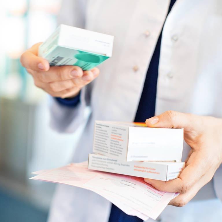 Medikamente Packungen und Arzneirezept in den Händen einer Person