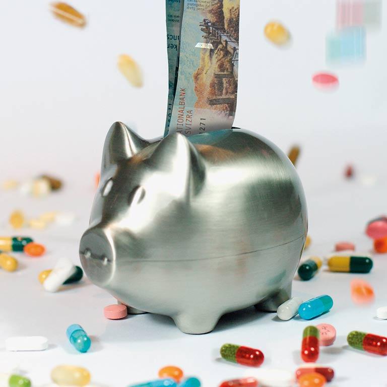 Chromstahl-Spaarschwein inmitten vieler farbiger Pillen