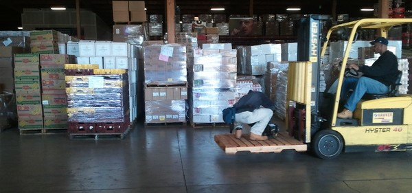 Man Riding on Pallet of Moving Forklift
