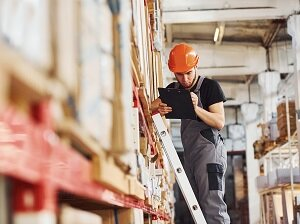 Warehouse Worker on Extension Ladder Taking Inventory with a Clipboard