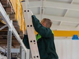 Warehouse Worker Climbing Extension Ladder