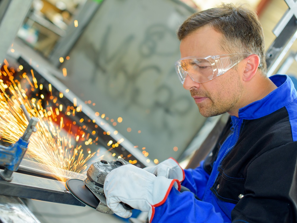 Worker Wearing Safety Glasses and Gloves in an Industrial Setting Using a Handheld Grinder Which is Creating Sparks