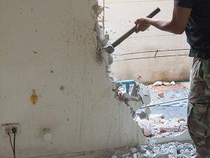 Worker Using Sledgehammer to Demolish a Wall
