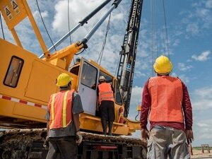 Construction Workers Near Crane Wearing Safety Vests