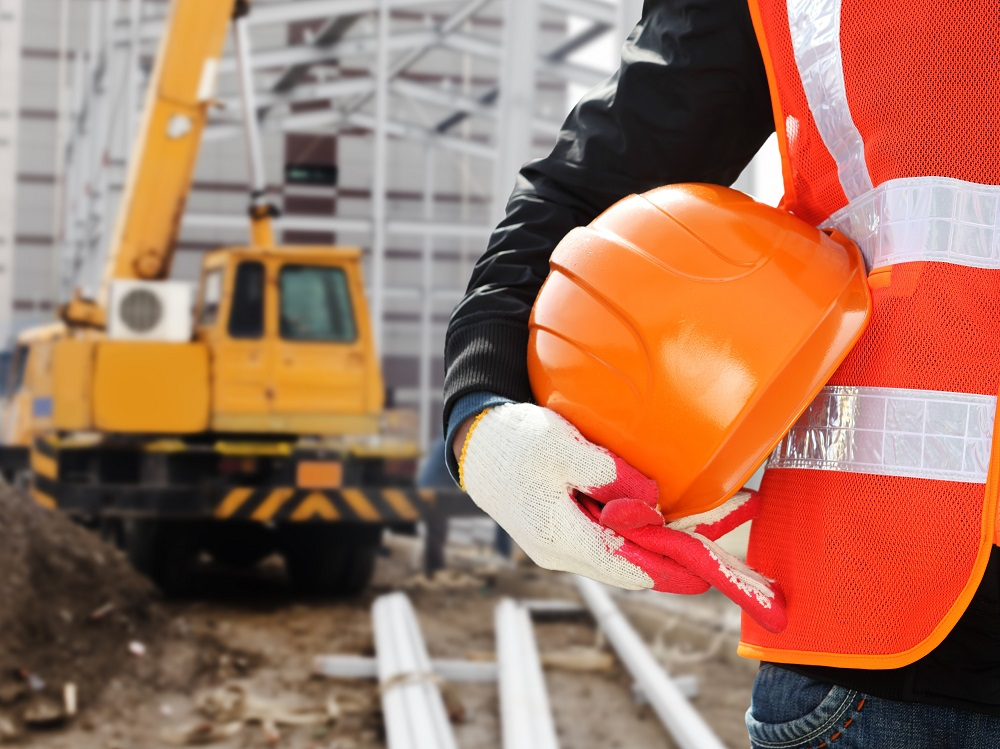 Construction Worker Standing at a Construction Site Wearing a Safety Vest and Holding a Hard Hat