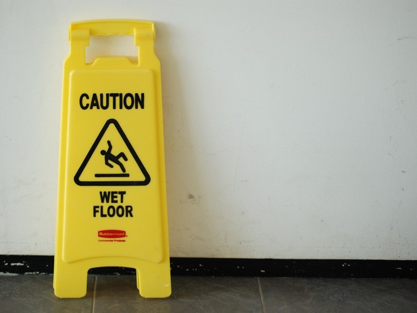 Portable Yellow Caution Wet Floor Sign Leaning Up Against a White Wall