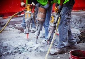 3 Construction Workers Using Jack Hammers Side by Side