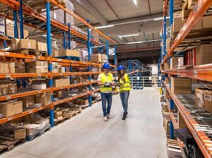 Two Workers Walking in Aisle of Warehouse