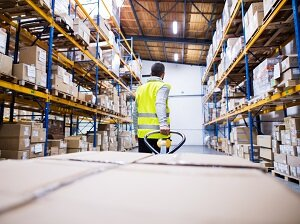 Warehouse Worker Pulling Pallet Jack in Warehouse
