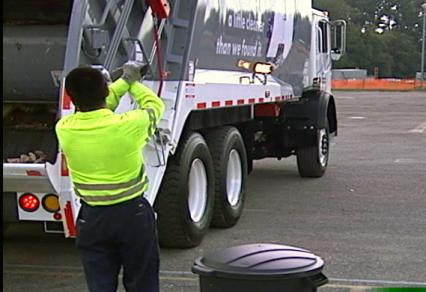 Spotter Helping Trash Truck Reverse