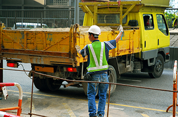 Spotter Helping Dump Truck Reverse