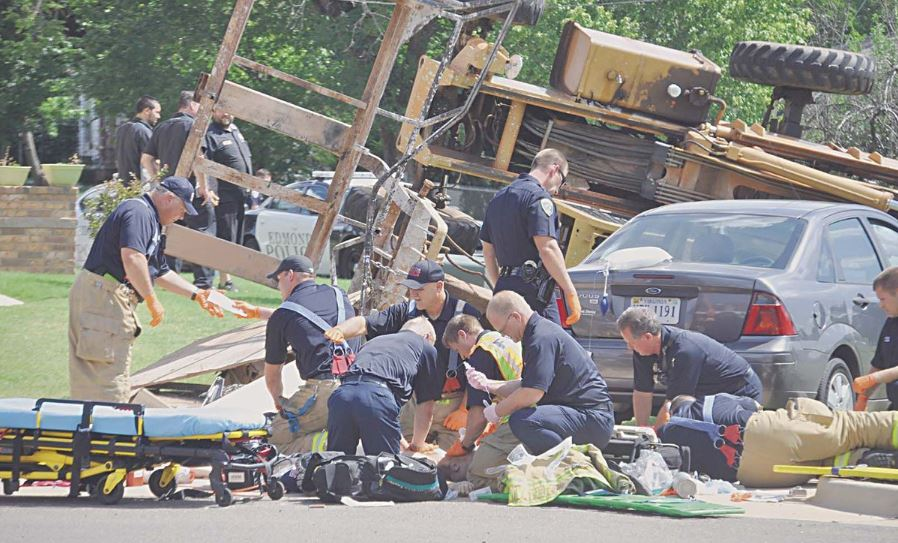 Emergency personnel responding to a fatal incident involving two construction workers killed when the forklift tipped over.