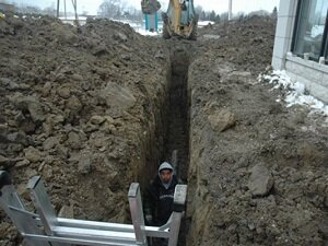 Man Standing in Deep Unprotected Trench