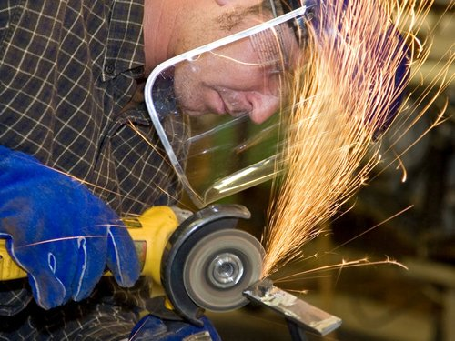 Worker Using Portable Grinder, Wearing Face Shield, Sparks Flying