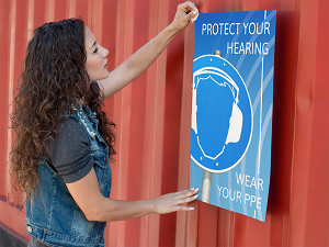 Woman Hanging PPE Poster on Red Wall