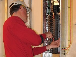 Electrician working in electrical panel