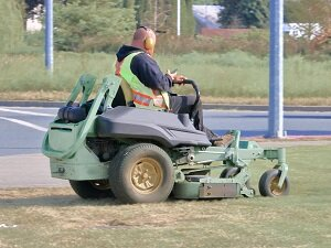 Landscaper looking at cell phone while riding a mower