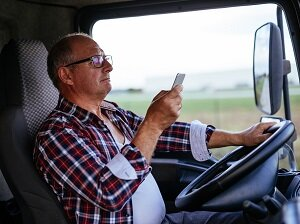 Trucker looking at cell phone while driving