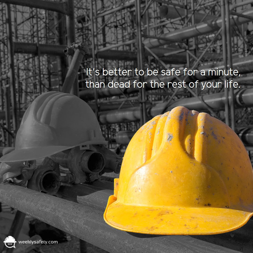 Two construction hard hats sitting on a table in a construction work site with one brightly colored yellow.