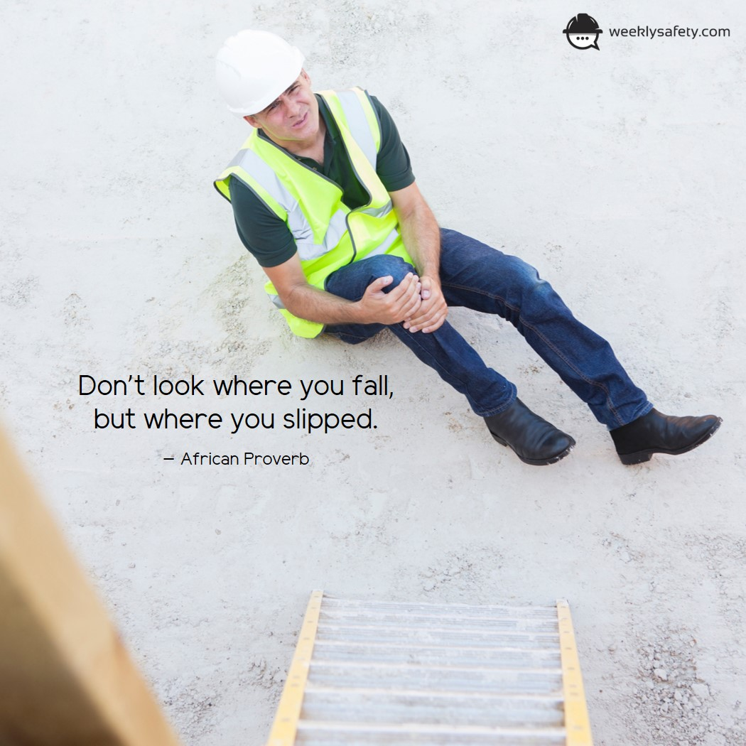 Construction worker sitting on ground grasping knee in pain.