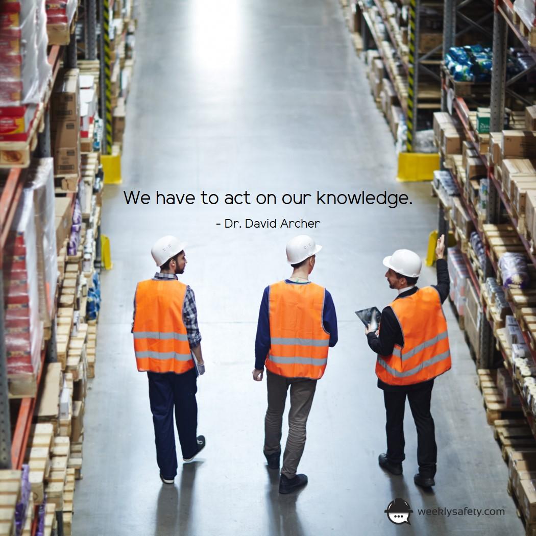 Three men walking through warehouse, white hard hats, orange safety vests