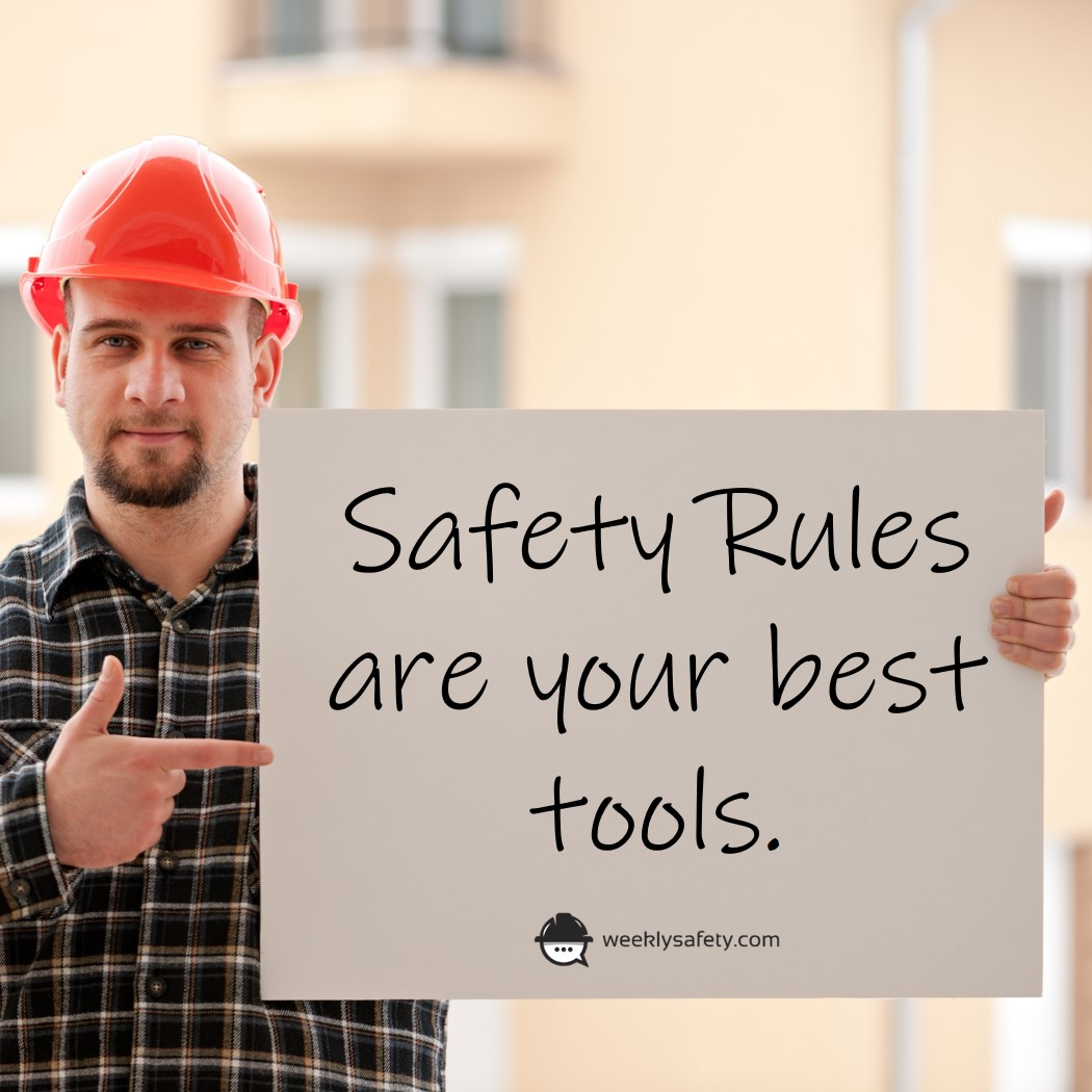 Construction man wearing hard hat pointing at a sign