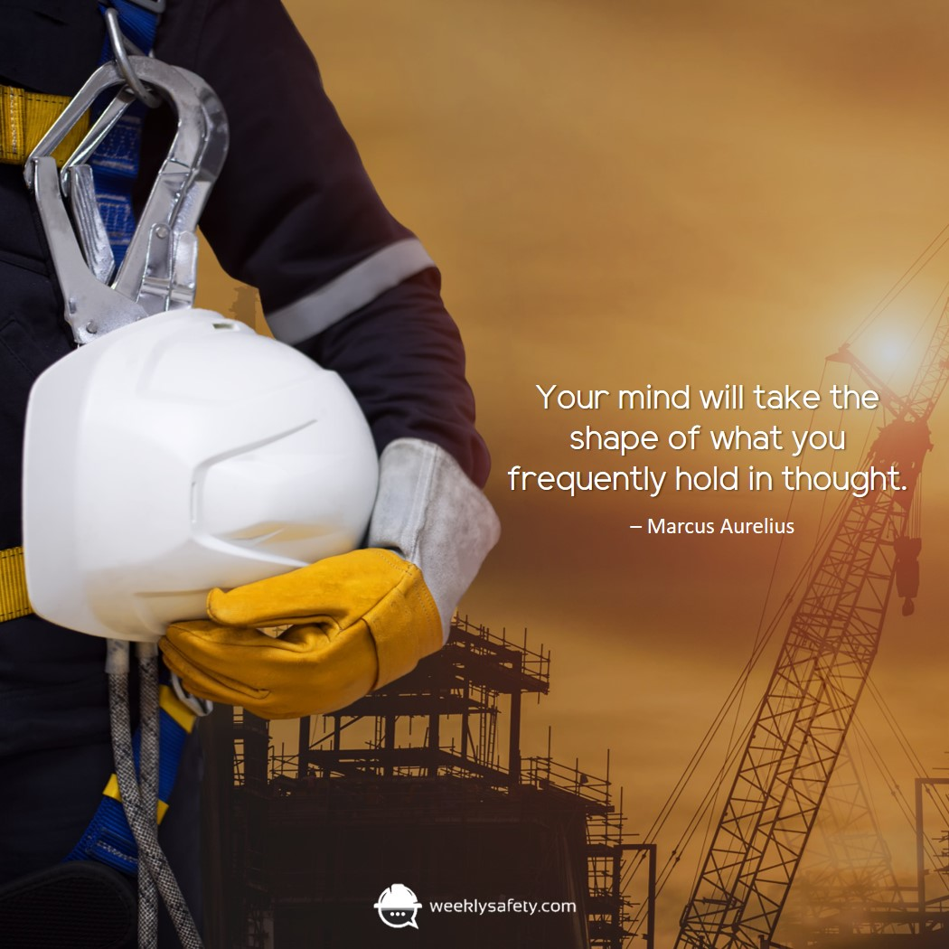 Construction worker holding a white hard hat while wearing thick working gloves.