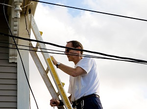 Man on Extension Ladder Near Power Lines
