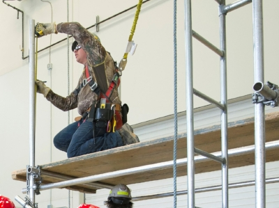 Trainee wearing personal fall protection on scaffolding.