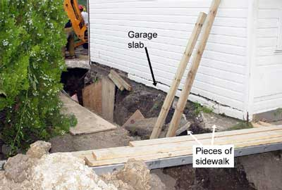 Pieces of sidewalk in the collapsed area and the garage slab foundation separated from the foundation. Notice, there is no protection in place to avoid the cave-in hazard.