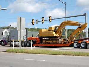 Truck Hauling Excavator Down City Street