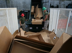 Two Workers Loading Cardboard into Recycler