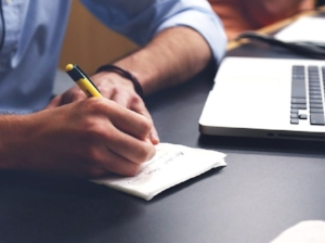 Office Worker Taking Notes on Paper, Laptop Nearby