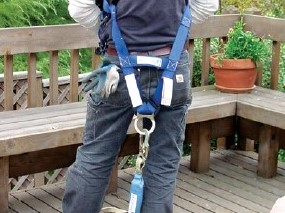 Construction Worker Inspecting, Then Wearing Personal Fall Protection System (PFAS)