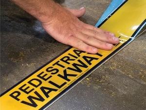 Laying Down Hazard Tape That Says Pedestrian Walkway