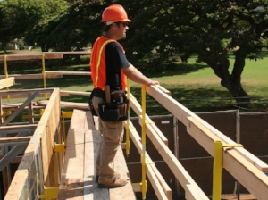 Construction Worker Standing Near Constructed Guardrail