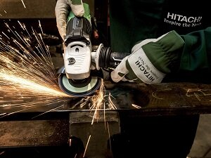 Worker Using Portable Grinder, Sparks Flying