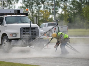 A worker uses pressurize air to clean out debris from the joints in the concrete.