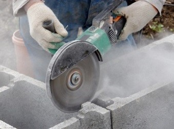 Worker Using Portable Grinder to Cut Stone, Creating Dust in the Air