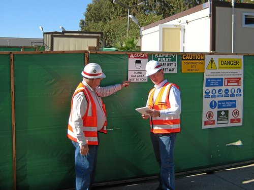 Construction Supervisors Evaluating Safety Signs at Job Site