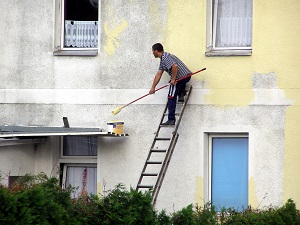 Man painting building on an extension ladder