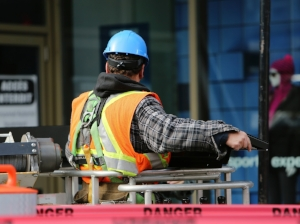 Construction Worker in Man Lift Wearing Hard Hat