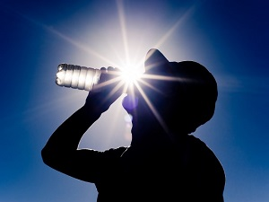 Worker Drinking Bottled Water in Heat