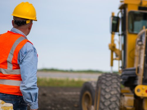 Construction Worker and Grader